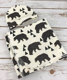 Our Baby Swaddle set is made from a geometric bear print in organic cotton knit. The material has a little stretch to make swaddling your little one simple. This listing includes a matching newborn size hat. The material is lightweight, but will keep baby cozy. A quality swaddle is a must have for keeping baby calm and happy.  Ready to ship. The swaddle measures approximately 32 by 32 and had rounded corners.  This makes a great gift for a baby shower or for babys arrival. It is also…