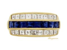 Oscar Heyman Brothers sapphire and diamond ring. Set to centre with a horizontal row of eight square channel set calibre cut natural sapphries in open back rubover settings with an approximate combined weight of 1.00 carat, flanked by two rows of channel set square baguette cut diamonds in open back rubover settings, all eighteen with an approximate combined weight of 1.00 carats, to a stepped three row band ring, conforming to the finger with a structured openwork gallery and intricate…
