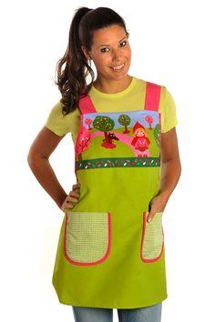 Estola con estampado en el canesú de caperucita combinado con tejido verde liso. Tiene dos bolsillos laterales. Se abrocha con cintas. Los tirantes van de contraste.