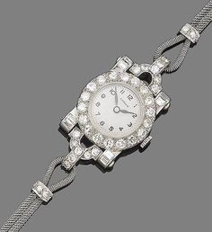 An art deco diamond watch, by Garrard, circa 1920 The circular dial with Arabic numerals, within an old brilliant-cut diamond surround, between old brilliant and baguette-cut diamond lugs, to a mesh-link strap highlighted by old brilliant-cut diamond spacers,
