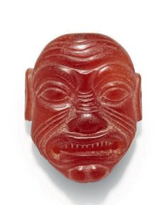 Neo-Assyrian Humbaba Amulet, 8th-7th Century BCThis carnelian head is carved with the grimacing and grotesque face of the Sumerian demon Humbaba. Heads like these were used as amulets since they were...
