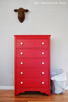 A tall red dresser with silver and white knobs