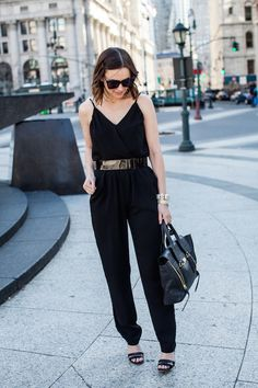 Shop this look for $174:  http://lookastic.com/women/looks/satchel-bag-and-heeled-sandals-and-watch-and-bracelet-and-belt-and-sunglasses-and-jumpsuit/3028  — Black Leather Satchel Bag  — Black Leather Heeled Sandals  — Gold Watch  — Gold Statement Bracelet  — Dark Brown Leather Belt  — Purple Sunglasses  — Black Jumpsuit