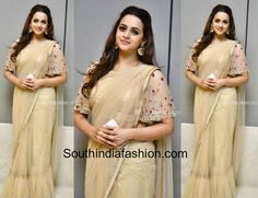 Actress Bhavana attended a wedding reception recently wearing a nude net saree that has ruffled hemline paired with matching floral embroidered ruffle sleeves blouse. A pair of gold chandbalis and half-up half-down hair rounded out her look! Bhavana Menon in sarees, kerala actress in sarees, Designer sari
