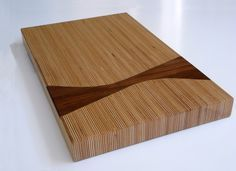 This sleek cutting board is made up of laminated Baltic Birch plywood with a walnut inlay. It is finished with a food safe mixture of bee's wax and walnut oil.