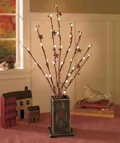 """Brighten up a room with the rustic charm of these Lighted Country Branches in Vase. The branches are decorated with LED lights, stars and berries. The branch bouquet rests in a vase with a 3-D accent on the front. On/off switch. Requires 2 """"AA"""" batteries"""