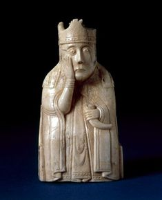 Chess-piece; walrus ivory; queen wearing floriated crown over veil, mantle; holding horn; right hand placed on cheek; seated in chair ornamented on back with adjacent leaf scrolls with animal-heads on top of uprights; chair sides: interlace ornament.