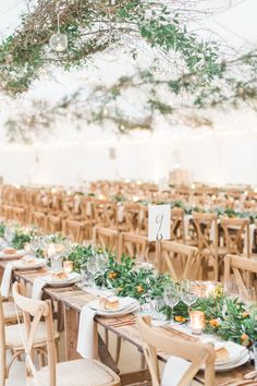Simple and earthy reception decor with lush green table runners and lots of low candles   Image by Amy Fanton Photography