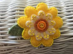 LYNN:  Felt brooch shaped like a flower in bright yellow and