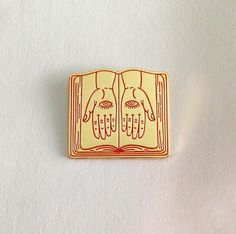 """1"""" wide, book-shaped, enamel lapel pin. Red outline on shiny gold enamel lapel pin with gold backing. Limited run! Ships in 1-3 days. All sale..."""