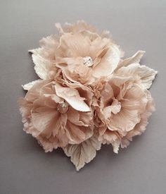 Centifolia is a ruffly rum pink silk chiffon petaled arrangement featuring champagne silk velvet flowers and leaves that are backed in ivory silk satin for added detail. These Emici Bridal flowers are created with silk chiffon that has been treated with Emici Bridal's exclusive millinery solution that creates soft, long lasting petals that are more resistant to fraying than some other blooms.Can be worn in the hair on a comb or attached to a ribbon for a gorgeous bridal sash. Swarovski…