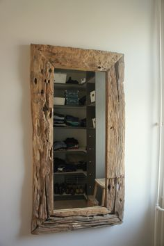 Spiegel van oud hout van Be Uniq met een inkijkje in de inloopkamer / inloopkast van Nieuwgraaf Kastenstudio. Interieurdesign: Angela Lanting Interieurstyling