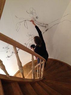 Artist Maartje van den Noort busy making a wallpainting in the staircase of our shop in Onderbergen.