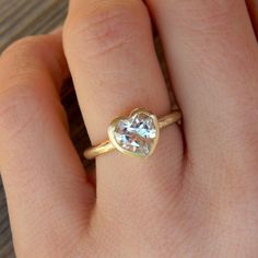 Reminds me of the ring I got for my Sweet 16. It was a heart shaped blue topaz.   HEART of GOLD, White Topaz and 14k Rose gold
