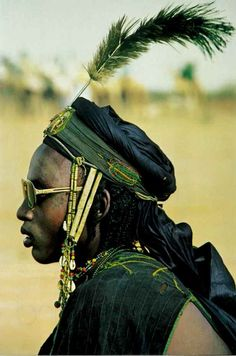 Africa | Among the Wodaabe men of Niger The very latest fashion, a pair of modern sunglasses, combines with brass and shell ornaments of a time-honoured Wodaabe headdress. | © National Geographic, November 1984. Article entitled 'Africa Adorned'. Text & Photos Angela Fisher.