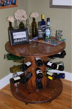 """DIY wine rack cable spool. Drilled holes with a 1 1/4"""" bit. Stained with minwax """"colonial maple"""" stain, wiped off and let dry. Then stained with minwax """"Jacobean"""", let dry and two coats of poly."""