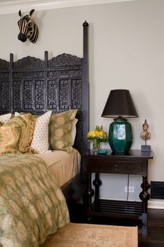 This vintage Moroccan screen was sprayed black and made into a custom four-poster bed. Notice the great color combination of green and black for this whimsical guest bedroom.