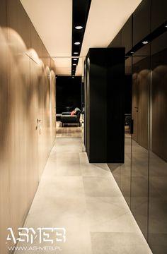 Zabudowa w holu widok z końca korytarza. 1: ściana szafa 475 x 255 x 60 z zastosowaniem frontów ze szkła lacobel w kolorze czarnym, szkło osadzone zostało w dyskretnych ramach aluminiowych lakierowanych na czarno, uchwyty Zobal U11M lakierowane na czarno 2. ściana fornirowana na całej długości przedpokoju (panele ścienne fornir dębowy bejcowany) drzwi wewnętrzne Secret fornirowane.