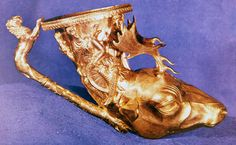 Beaten gold drinking vessel in the form of a stag's head, with goddesses around the upper rim and a lion-tipped handle.
