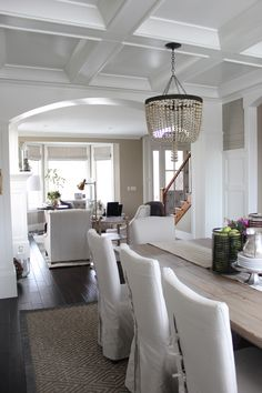 interiors by alice lane home collection | linen slipcovered chairs, dark wood flooring, white paneling, white wainscoting, grasscloth wallpaper
