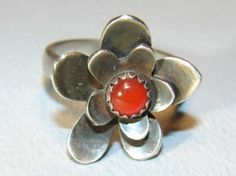 This is a small Flower Ring hand sawed from 18 gauge Sterling Silver features a Genuine 3mm Red Coral Stone in the center. The flower was cut out in two distinct pieces, shaped, and soldered together