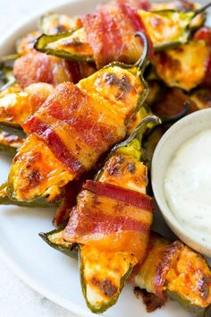 A plate of bacon wrapped jalapeno poppers served with ranch dressing.