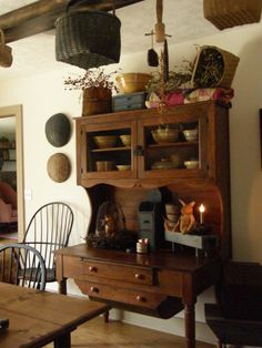 Prim...love the cupboard & hanging baskets.