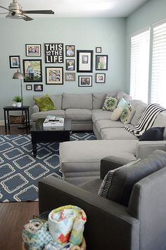 EXACTLY what I want for the living room (reversed)! Sectional couch against window/wall... And family photos on side wall :D