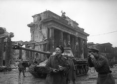 The acclaimed Russian-Jewish war photographer Yevgeny Khaldei (center) and a Russian soldier take photos at the Brandenburg Gate after the fall of Berlin in 1945.