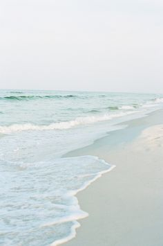A light gray-blue sky, white sand beach, pale aqua water edged in seafoam... simply beautiful nature at her best.