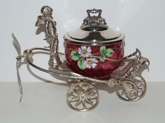 "Enameled Cranberry pickle castor in a Figural silver plated ""Chariot"" frame with wheels marked Simpson Hall Miller# 0650.  $1,450"