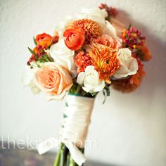 A white, cream, and orange bouquet of dahlias (they're in-season during the fall) and roses packed tightly and wrapped with cream ribbon.