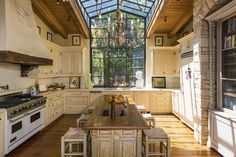 Spacious kitchen designed in the French country style features a large window which reaches up into the skylight [5690 3793] http://ift.tt/2bJhc99
