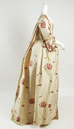 Fashion from 18th century ball gown dress Robe a la Francaise circa from British, England in 1750-1775. #Historical #Costume made from cream silk fabric brocade with woven flowers floral pattern. Square neck at the front bodice with matching stomacher, long ruffles frills sleeves. The skirt is open at the front, and away from the waist towards the sides of the skirt with a petticoat underneath. Self fabric ruffles lace is used on the robes. #Baroque #Rococo #Vintage #Fashion