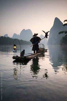 Fisherman with cormorants on the Li river, near Guilin, China by Matteo Colombo. An exclusive image for Stocksy.com.