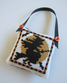 Completed Cross Stitch Halloween Ornament Hand-stitched by me Pattern from Prairie Schoolers Pumpkin Patch leaflet Pillow-type ornament with black and dark orange gingham backing, finished with a black grosgrain ribbon hanger and two orange accent buttons. Approximately 2 1/4 square.
