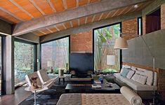 Era uma casa escura e úmida. Mas que encantou Flavia Petrossi pela arquitetura modernista. Na reforma, ela aumentou a entrada de luz natural com esquadrias de vidro  que chegam até a laje pré-fabricada