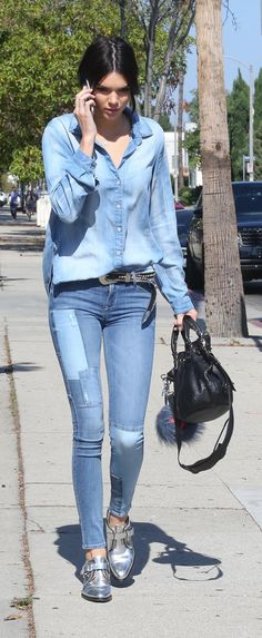 Kendall Jenner wears a chambray top, patched denim jeans, metallic silver loafers and a black purse