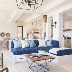 The family area features a custom built-in sectional with cushions in a jaunty Ralph Lauren Home stripe and a pair of Henredon armchairs  with Soane fabric on the cushions. The chandelier, coffee table and carpet are also custom. Shining down on the grouping is a swingarm  light from Visual Comfort & Co. In the dining area beyond, the designer paired custom tables and a banquette, upholstered in a Kravet fabric, with Sika Design chairs and a Currey & Company light. Minimalist House Design, Minimalist Home Decor, Coastal Living Rooms, Living Room Decor, Living Spaces, Decoration Design, Contemporary Home Decor, Modern Kitchen Design, Home Interior Design