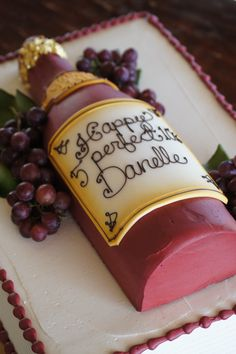 Red wine bottle shaped birthday cake with grapes