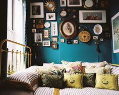 Eclectic Bedroom - Lotsa pictures and pillows! A gallery wall of small artworks above a bed with striped bedding