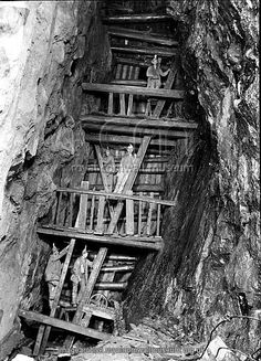The Man Engine at 234 fathoms level below adit, in 1893 Dolcoath Mine, Camborne, Cornwall. 1893 The Man Engine at 234 fathoms level below adit, in 1893. It went down to the 314 level. Miners can be seen standing on the steps of the engine rod while others stand on solars or platforms fixed in the shaft at intervals of 12 feet (the man engine went down to the 314 fathom level). The man engine made 5 strokes a minute, thus enabling men to ride up or down 60 feet a minute. Ordinary ladders were…