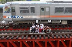 2013.09.03 - Women got a ride on man-powered trolley on a track near an oil depot as a train passed by in Manila Tuesday. (Francis R. Malasig/European Pressphoto Agency)
