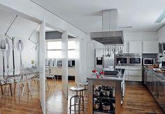 A cozinha tem bancada de inox e ilha central. Repare no detalhe da coifa, com suporte para utensílios