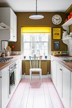 A narrow galley kitchen with white cabinets and green paint pink wooden floor. Small Kitchen design ideas - worktops, to units, cupboards, sinks, lighting and wallpaper from House & Garden.