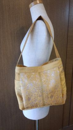 銀糸 花柄の帯をリメイクしました<横約30㎝ 深さ約25㎝ 底厚さ約8㎝ 持ち手約54㎝>口は中央をマグネット止め、肩掛けタイプのバッグです裏はドット柄の綿ブ...|ハンドメイド、手作り、手仕事品の通販・販売・購入ならCreema。
