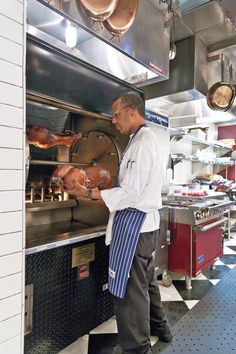 R'evolution's executive sous chef Erik Veney tends to meats roasting in a J rotisserie. - Sara Essex Bradley