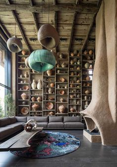 Entire wall displaying a vast collection of ceramics in a double height living room that has a fireplace with an organic design, Kozyn, Kyiv Oblast, Ukraine - Home Design and Decoration Deco Restaurant, Thatched Roof, House Roof, Living Room Designs, House Design, Interior Design, Interior Ideas, House Architecture, Contemporary Architecture
