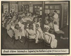 A librarian telling an Ojibwa legend to a roomful of children at the Queens Borough Public Library, 1910