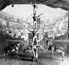 A music hall show at London's Empire Theatre (1898). Seven acrobats perform a balancing feat, with the help of two horses.